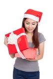 A menina asiática com o chapéu vermelho de Santa abre uma caixa de presente e um sorriso Fotos de Stock Royalty Free