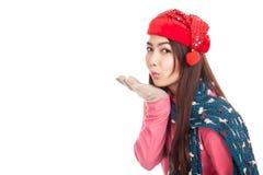 Menina asiática com o chapéu vermelho do Natal que funde um beijo Fotografia de Stock