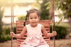 Menina asiática da criança que tem o divertimento para jogar o balanço no campo de jogos Fotografia de Stock