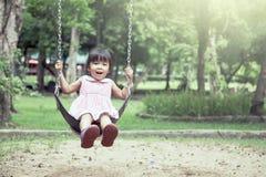 Menina asiática da criança que tem o divertimento para jogar o balanço no campo de jogos Imagens de Stock