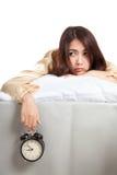 A menina asiática sonolento acorda no humor mau com despertador Fotografia de Stock Royalty Free