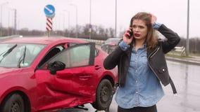 Menina assustado que fala no telefone depois que um acidente de tr?nsito na chuva, carro ? quebrado video estoque