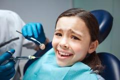 A menina assustado senta-se na cadeira dental na sala Ela receosa da dor do dentista e de dentes As mãos adultas guardam ferramen foto de stock royalty free