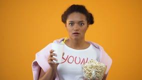 Menina atentamente que olha o filme e que bebe o refresco, influência da televisão filme