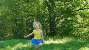 A menina ativa está correndo no parque que joga fora na grama verde filme