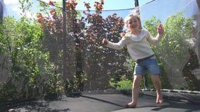 Menina ativa que faz os truques que saltam no trampolim Tiro Handheld video estoque