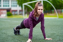 Menina ativa que pratica a pose da prancha da ioga para os músculos abdominais no verão que vive fora uma vida do ajuste fotografia de stock