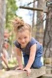 Menina ativa que tem o divertimento no parque da corda Imagens de Stock