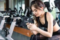 Menina ativa que usa o smartphone no gym da aptidão imagem de stock royalty free