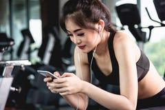Menina ativa que usa o smartphone no gym da aptidão foto de stock