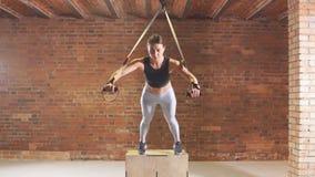 A menina atlética é contratada no fogo cruzado Um atleta novo é contratado com um trx no gym video estoque