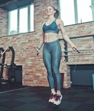 Menina atlética alegre no treinamento da mulher do sportswear com uma corda de salto imagem de stock royalty free