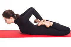Menina atlética bonita no terno preto que faz a ioga asana do bhekasana - pose da rã Isolado no fundo branco Imagem de Stock Royalty Free