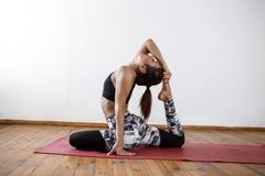 Menina atlética bonita nova que pratica asanas internos da ioga Pose de Eka Pada Rajakapotasana, rei Um-equipado com pernas Pigeo fotografia de stock royalty free