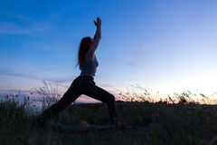 Menina atlética bonita que faz a ioga contra o mar Fotografia de Stock Royalty Free