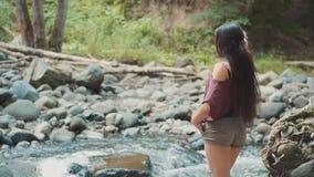 A menina atlética bonito admira a natureza e o rio da floresta da montanha, uma senhora com pele do problema joga acima seu longo video estoque
