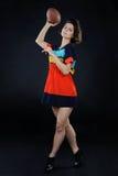 Menina atlética com uma bola no vestido colorido no estúdio em vagabundos escuros Fotografia de Stock Royalty Free
