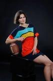 Menina atlética com uma bola no vestido colorido no estúdio em vagabundos escuros Imagens de Stock