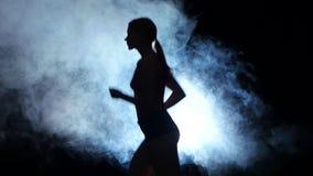 Menina atlética da aptidão que corre em um fundo preto iluminado pelo projetor no fumo Silhueta filme