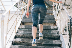 A menina atlética delgada escala as escadas imagem de stock royalty free