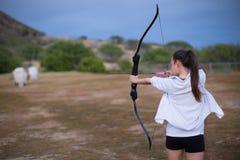 Menina atlética e atlética que aponta uma curva e uma seta em uma escala do tiro ao arco fotografia de stock
