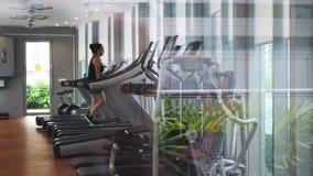 Menina atlética em uma escada rolante na frente da janela no gym Movimento lento 3840x2160 video estoque