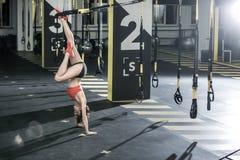 A menina atlética está de cabeça para baixo no gym Imagens de Stock Royalty Free