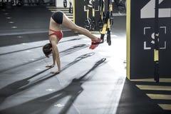 A menina atlética está de cabeça para baixo no gym Foto de Stock