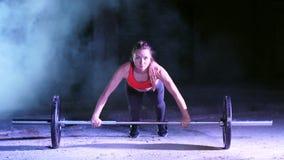 A menina atlética está fazendo empurra levanta com um barbell, na noite, no fumo claro, névoa, à luz dos holofotes coloridos, den video estoque