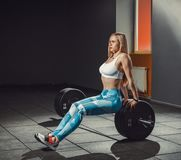 Menina atlética europeia 'sexy' da aptidão que dá certo no gym A mulher da aptidão senta-se no barbell ou na carne sem gordura no fotos de stock