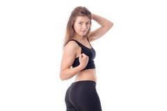 A menina atlética nova na roupa preta vale o giro lateralmente e manteve a bola para o cabelo isolado no fundo branco Imagem de Stock