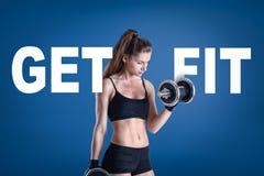 Menina atlética nova no sportswear preto com um peso e PARA OBTER o sinal da FIT no fundo azul imagens de stock royalty free