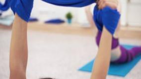 Menina atlética nova que estica em uma rede azul da aptidão filme