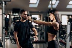 Menina atlética que faz o exercício para os músculos dos braços com peso no gym sob a supervisão de um treinador foto de stock