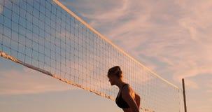 Menina atlética que joga saltos do voleibol de praia no ar e nas greves a bola sobre a rede em uma noite bonita do verão video estoque