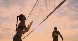Menina atlética que joga saltos do voleibol de praia no ar e nas greves a bola sobre a rede em uma noite bonita do verão vídeos de arquivo
