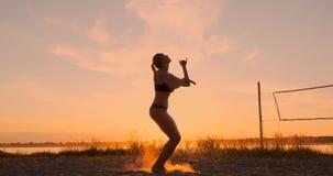 Menina atlética que joga saltos do voleibol de praia no ar e nas greves a bola sobre a rede em uma noite bonita do verão filme