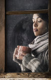 Menina atrás da janela com uma xícara de café ou um chá Foto de Stock Royalty Free