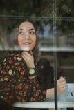 A menina atrás da janela do café Imagens de Stock Royalty Free