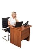 Menina atrás da mesa com um portátil Fotografia de Stock Royalty Free