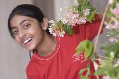 Menina atrás das flores imagem de stock
