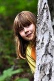 Menina atrás de uma árvore Fotos de Stock Royalty Free