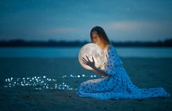 A menina atrativa bonita em uma praia da noite com areia e estrelas abraça a lua, fotografia artística foto de stock royalty free