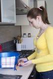 Menina atrativa com as braçadeiras na cozinha Fotografia de Stock Royalty Free