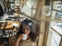 A menina atrativa com cabelo encaracolado senta-se em um café na tabela e no café das bebidas imagens de stock