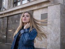 Menina atrativa com cabelo lindo em um revestimento da sarja de Nimes contra o contexto de uma construção moderna fotografia de stock royalty free