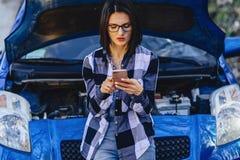 menina atrativa com a capa aberta próxima do telefone do carro imagens de stock royalty free