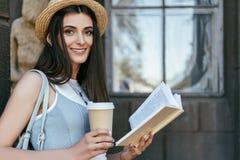 menina atrativa com o livro e o sorriso de leitura do copo de papel imagem de stock royalty free