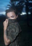 Menina atrativa com o revestimento militar do estilo isolado no campo verde Imagem de Stock
