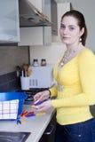 Menina atrativa com os roupa-Pegs na cozinha Foto de Stock